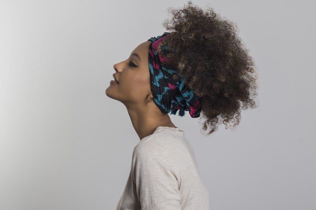 Mulher com cabelo cacheado preso com turbante