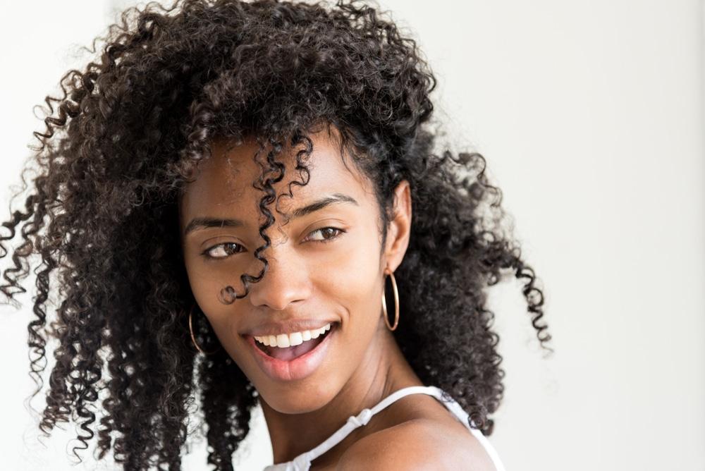 jovem sorridente com cabelos lindos, crespos e volumosos