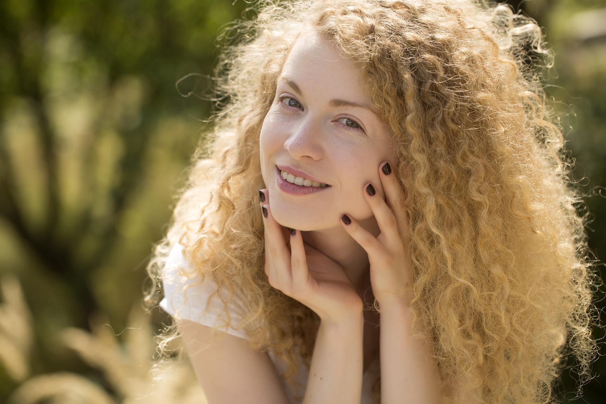 mulher loira de cabelo crespo solto