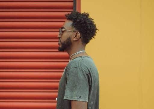 Homem com corte de cabelo crespo, com corte degradê