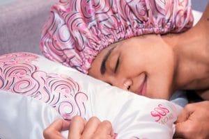 Mulher usando touca de cetim e com o rosto em almofada com fronha de cetim