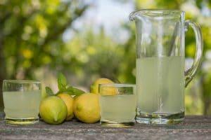 jarra com suco de limão e limões do lado