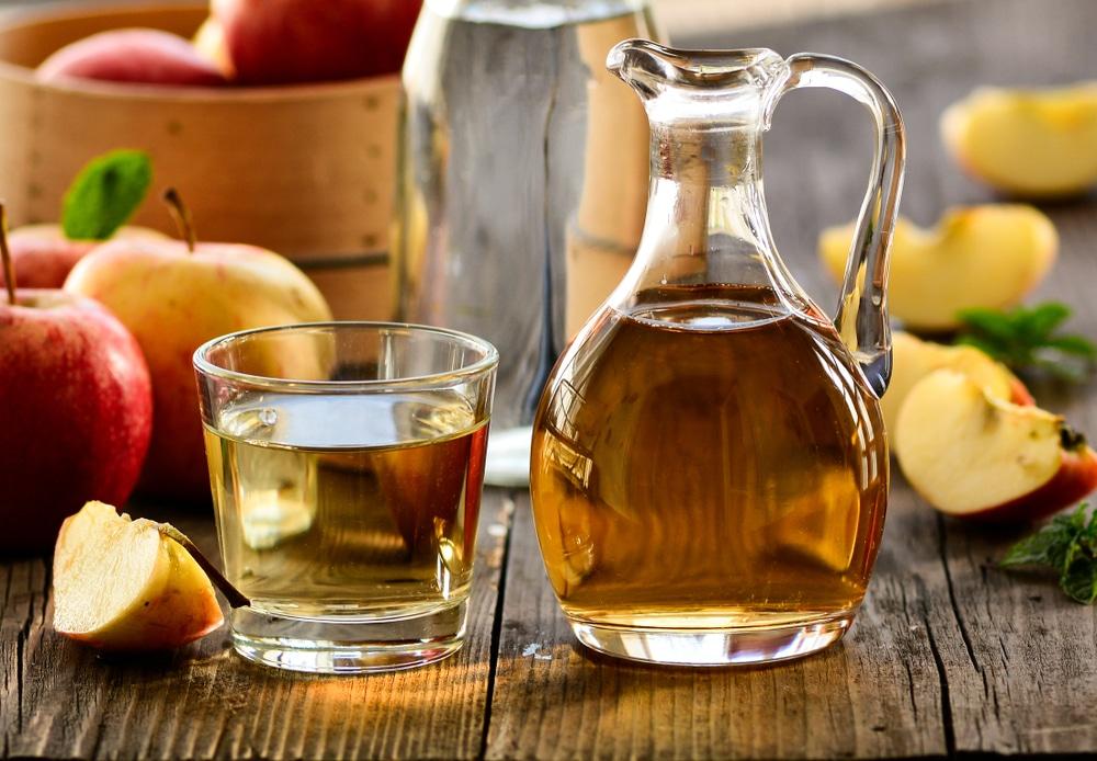 Jarro e copo com vinagre de maça em cima de mesa de madeira