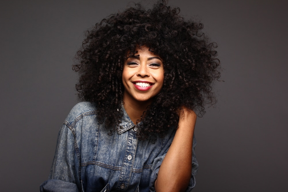 mulher negra com cabelos longos cacheados e volumosos