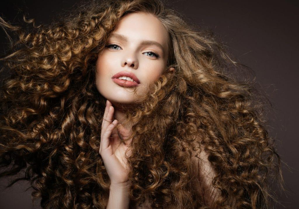 Mulher jovem com lindos cabelos cacheados, longos, loiros e volumosos