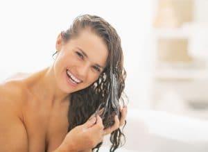 mulher passando condicionador nos cabelos