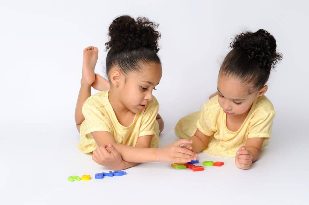 Crianças irmãs gêmeas com os cabelos com o mesmo penteado
