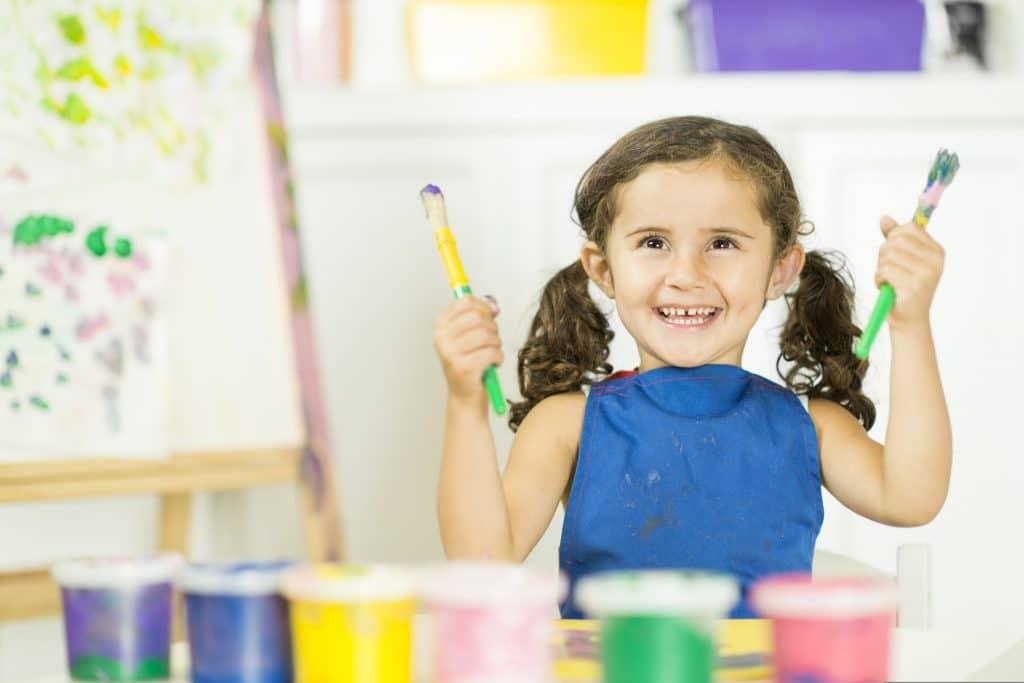 Criança com penteado se divertindo fazendo pintura