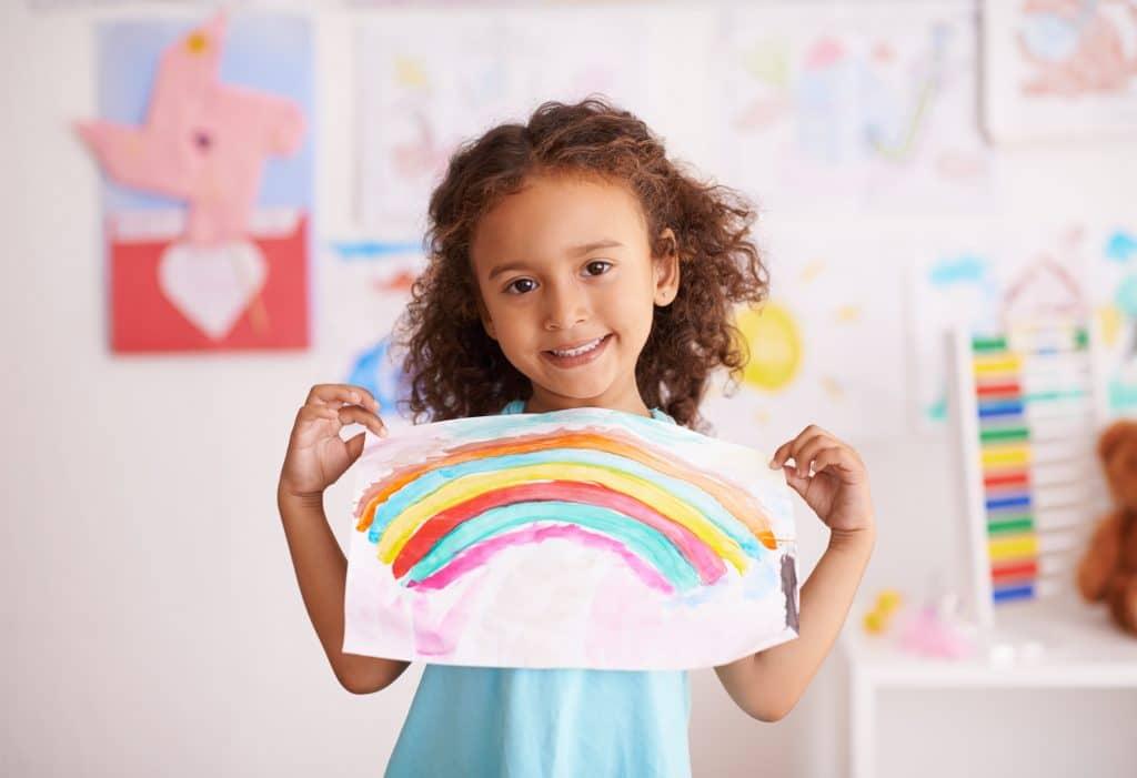 Criança segurando desenho e usando os cabelos com um penteado semi preso
