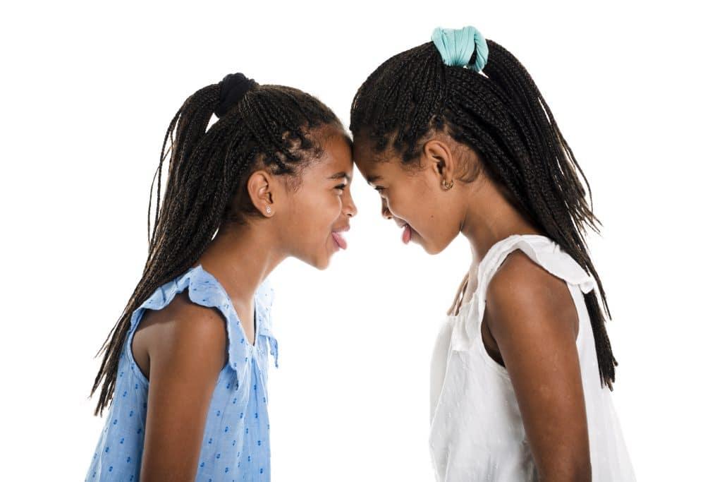 2 Crianças com cabelos trançados fazendo careta uma para a outra