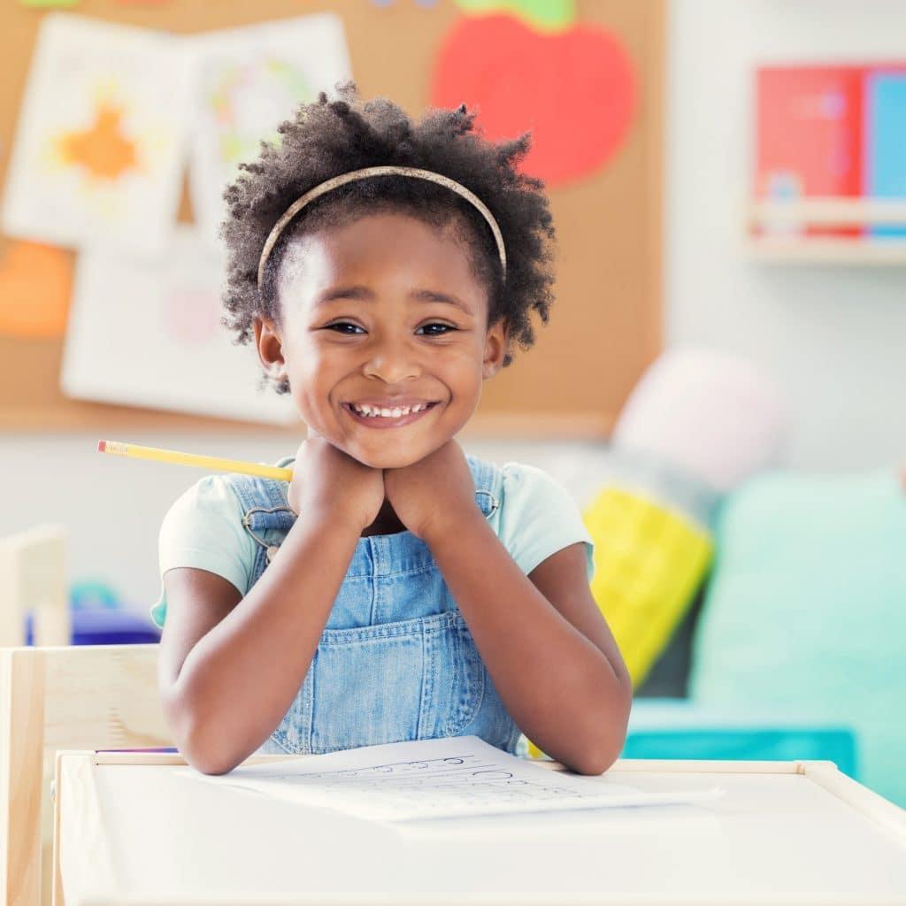 Criança com cabelos crespos, bonitos e volumosos sorrindo