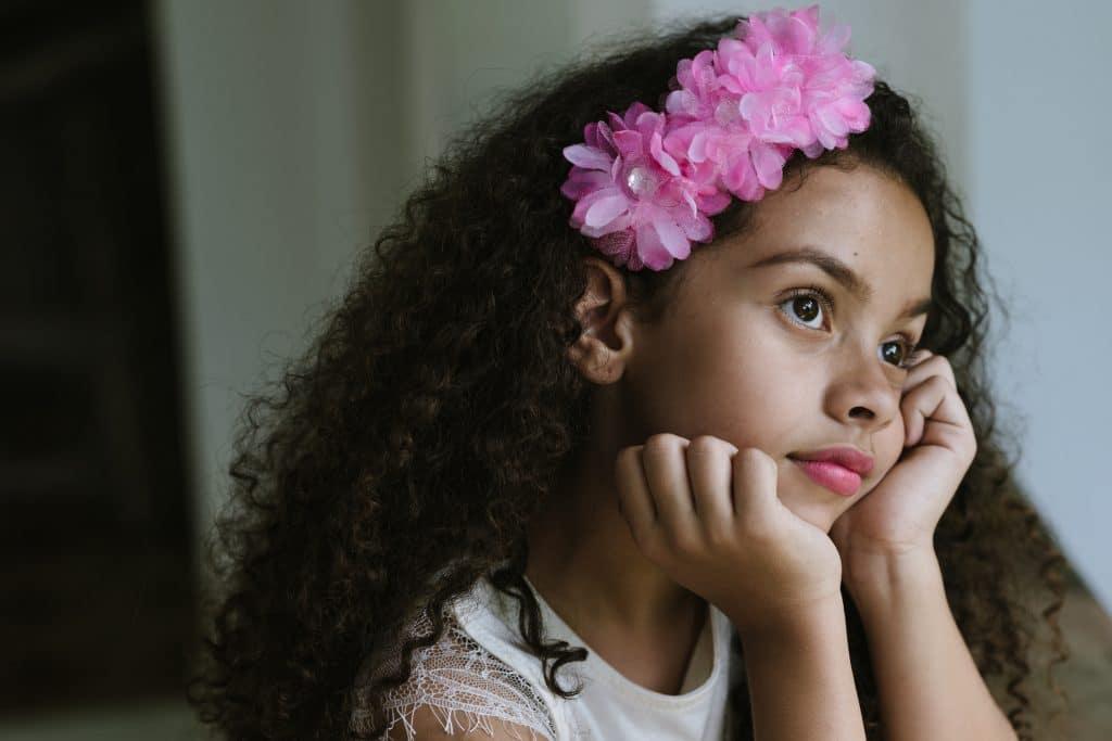 Criança com cabelos crespos, bonitos e volumosos olhando para janela