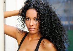 mulher com cabelos cacheados longos e negros