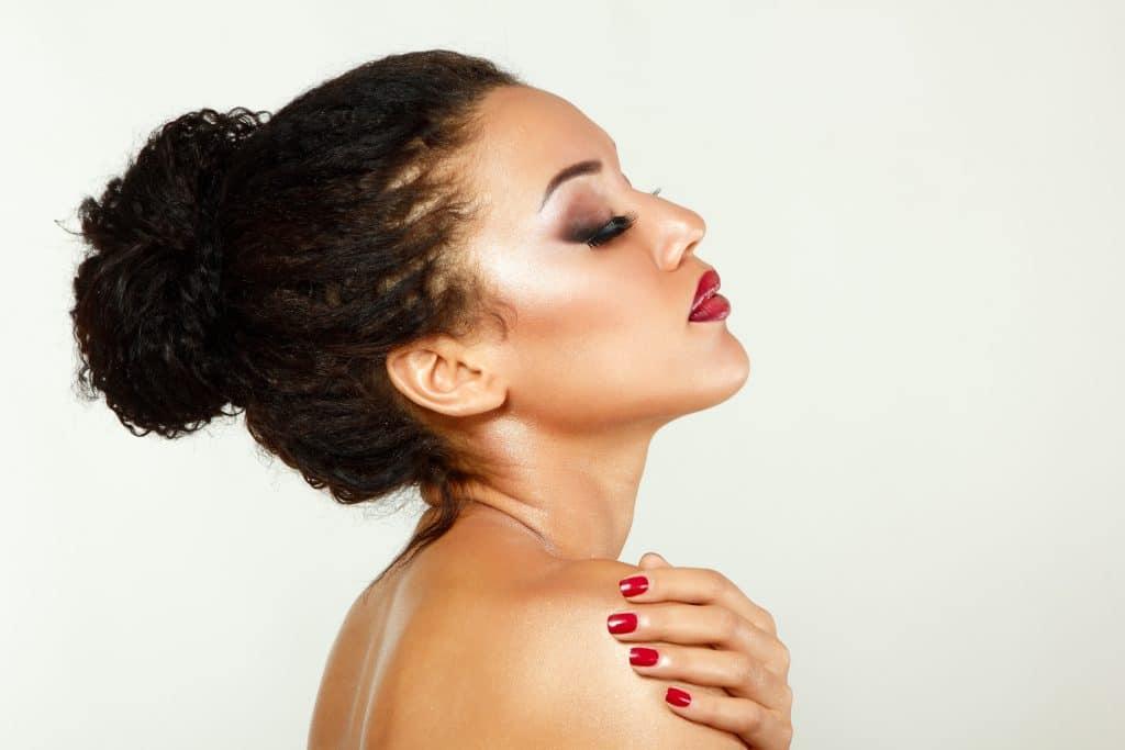 mulher com penteado cabelo curto cacheado: coque alto