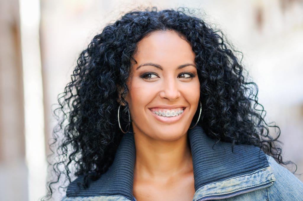 Mulher jovem com cabelos longos cacheados na cor preto azulado