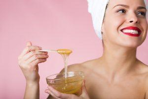 Mulher segurando um recipiente com mel