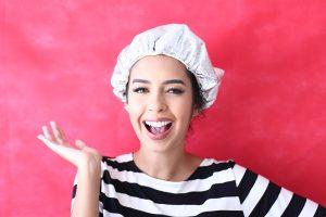 youtuber Jliana Louise com touca na cabeça fazendo uma umectação capilar