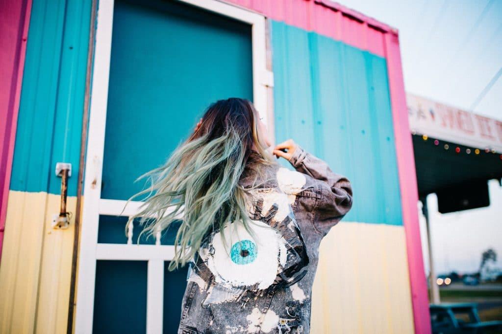 jovem com cabelos cacheados na cor azul