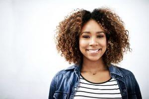 Mulher jovem com luzes em cabelo cacheado