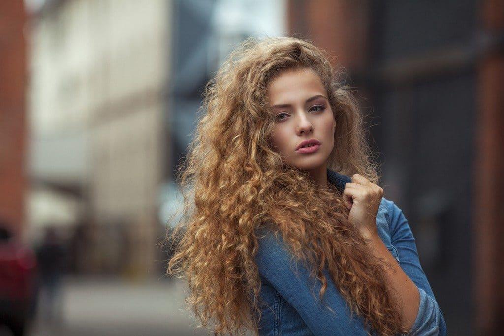Mulher jovem com cabelo ondulado e corte em camadas longas
