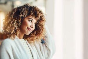 Mulher jovem com cabelo cacheado loiro e corte com franja