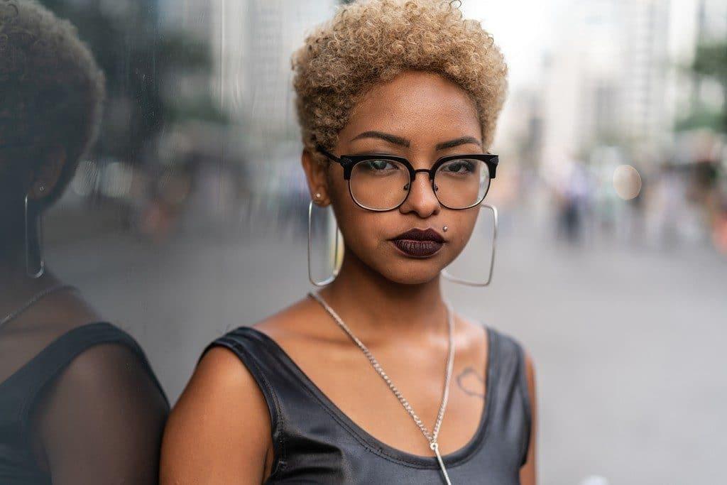Mulher jovem com cabelo crespo, loiro e corte pixie cut