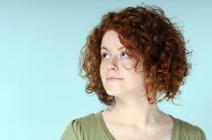 Mulher com cabelo ondulado loiro, curto