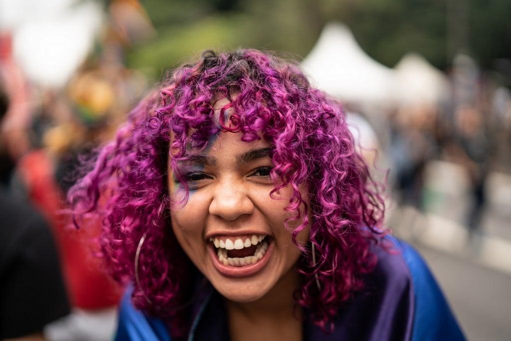 Mulher jovem com cabelo cacheado rosa