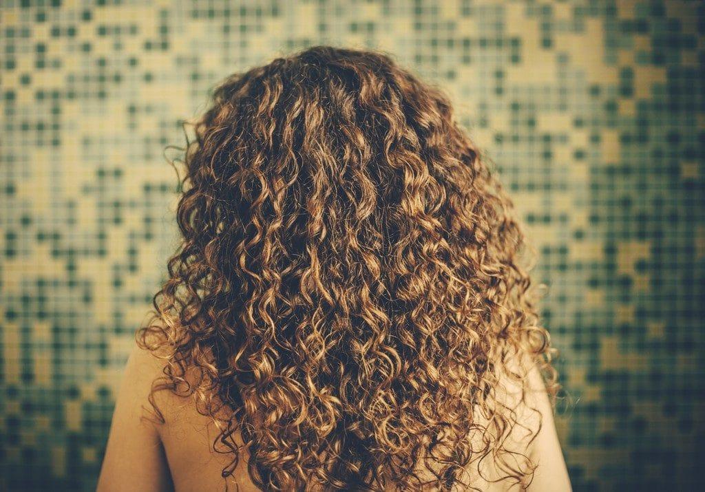 Mulher, virade de costas, com cabelo cacheado loiro