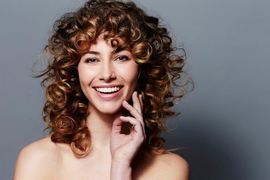 Mulher jovem com cabelo cacheado com mechas