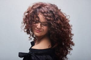 Mulher com cabelo cacheado marsala