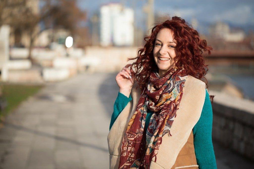 Mulher com cabelo ondulado curto marsala