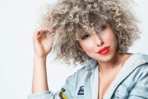 Mulher jovem com cabelo crespo loiro platinado