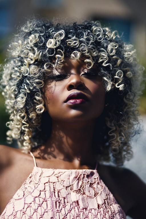 Mulher jovem com cabelo cacheado loiro platinado