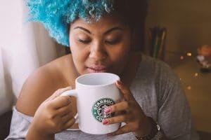 jovem negra com cabelos cacheados na cor azul