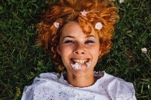 Mulher jovem com cabelo ondulado ruivo, deitada na grama