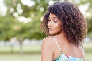Mulher de cabelo cacheado com franja