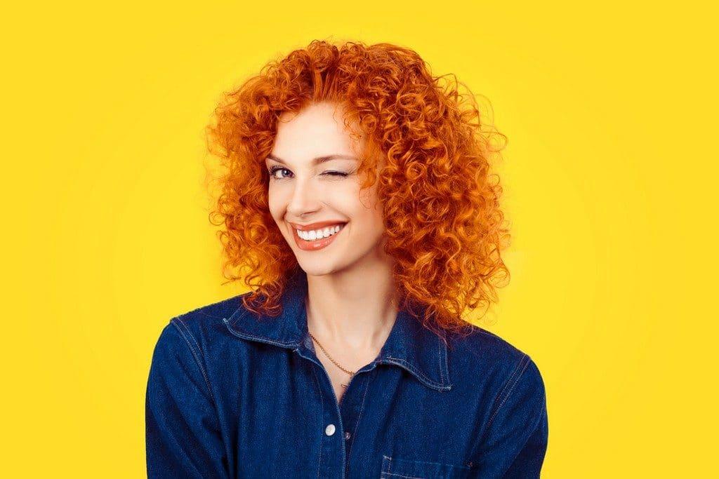 Mulher com corte de cabelo cacheado médio