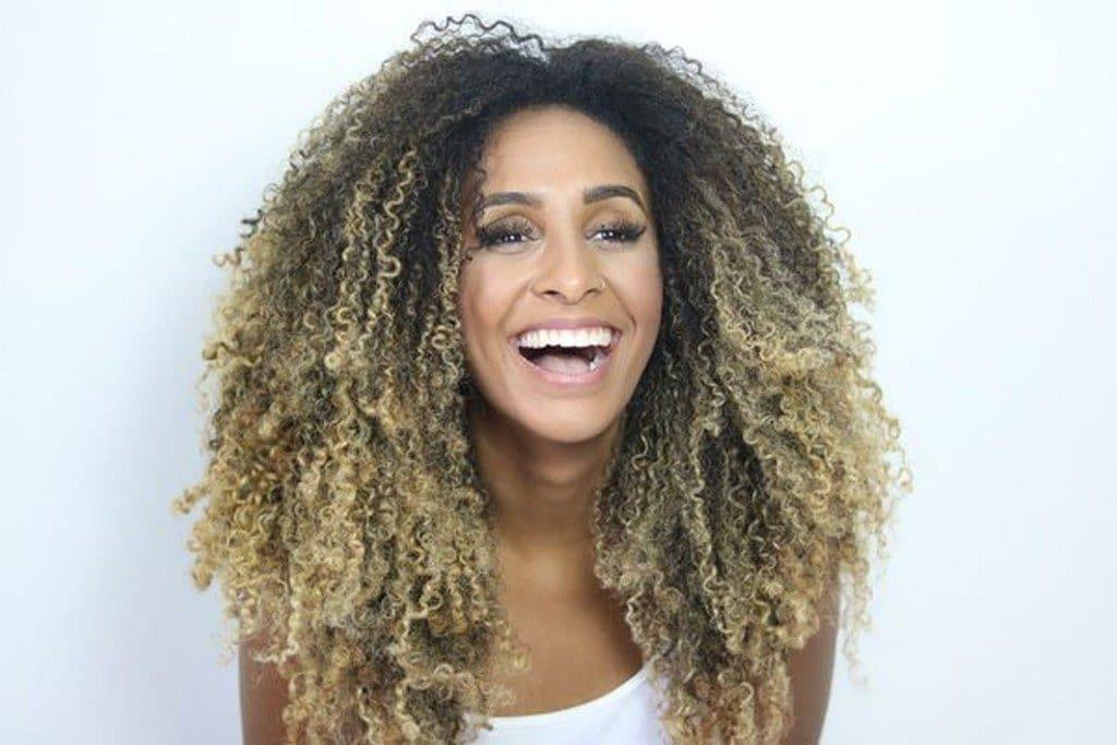 Mulher jovem de cabelo cacheado com luzes