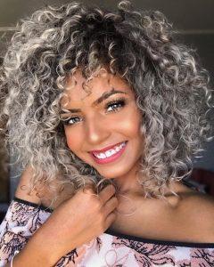 Mulher jovem de cabelo cacheado com luzes platinadas