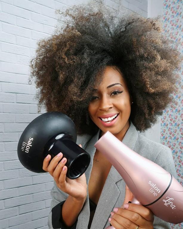Mulher de cabelo crespo, segurando um secador e um difusor