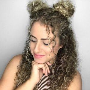 Mulher de cabelo cacheado, com penteado space bun