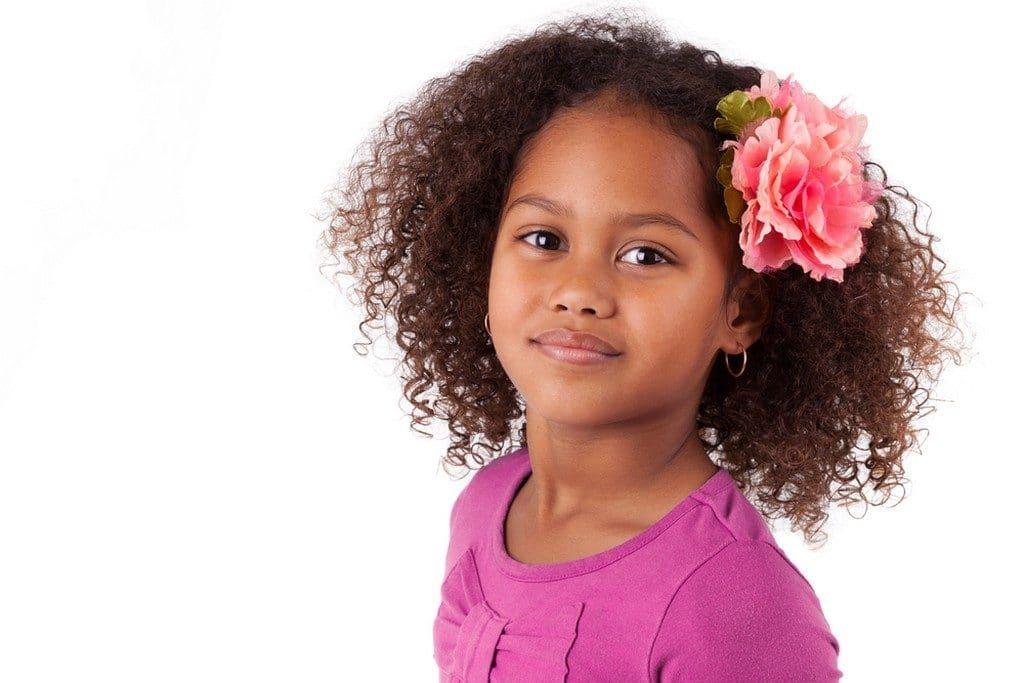 Garotinha de cabelo cacheado solto e flor na lateral
