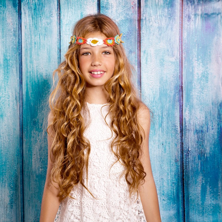 Garotinha com cabelo ondulado, longo, loiro, solto com uma tiara de flor