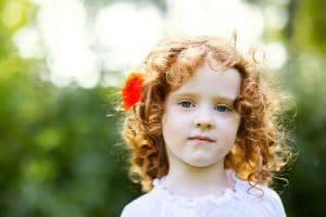 Garotinha com o cabelo ondulado, loiro, solto com uma flor