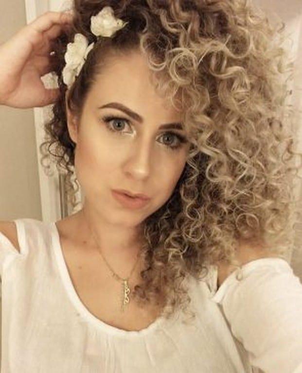 Mulher de cabelo ondulado solto, de lado, com tiara de flores brancas