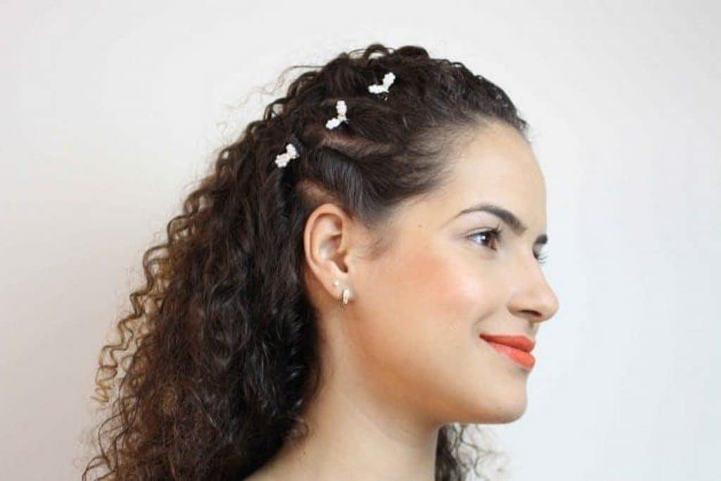Mulher de cabelo cacheado, longo, solto, com torcidinhos laterais e presilhas