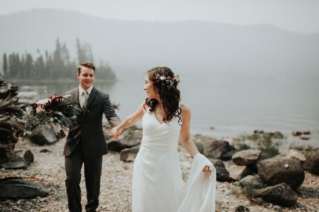 Noivos dando as mãos; noiva de cabelo solto, com acessório lateral
