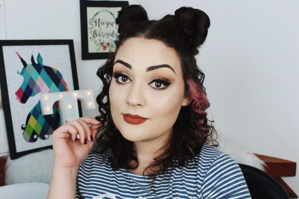 Mulher de cabelo ondulado com penteado space bun