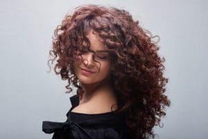 Mulher de cabelo cacheado, longo, com corte em camadas